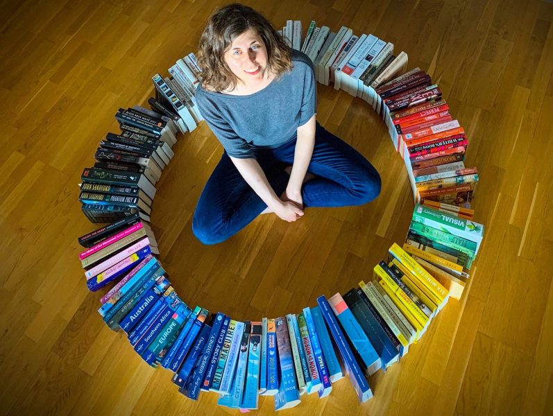 Ashley Kalagian Blunt surrounded by colourful books arranged in a circle rainbow