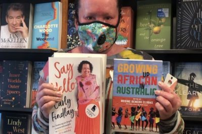 Carly Findlay wearing a breathing mask holding books