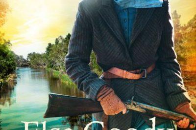 Elsa Goody Bushranger: a woman stands holding a rifle while walking along a river