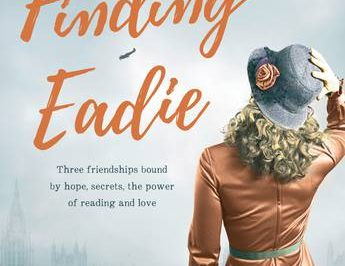 Finding Eeadie: a woman stands, holding her hat while looking up at the sky