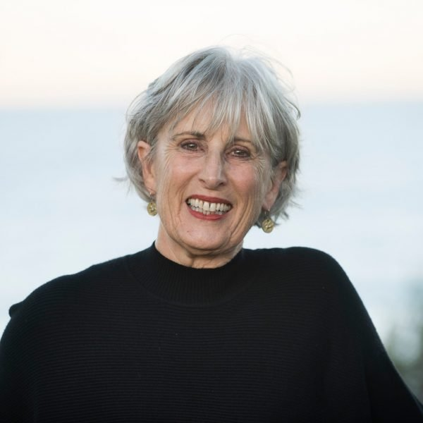 Amanda Hampson smiles into the camera. She's in her early 60s with short grey hair and a black top