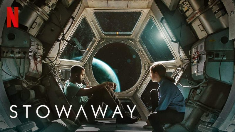 Stowaway: the stowaway and the doctor sit next to a window in space showing earth