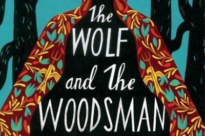 the wolf and the woodsman: trees frame a female figure whose cloak has a folk art pattern